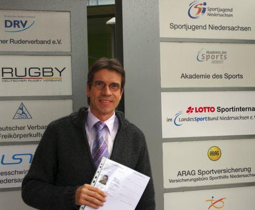 Thomas Ruminski mit Trainerzertifikat vor der Akademie des Sports in Hannover